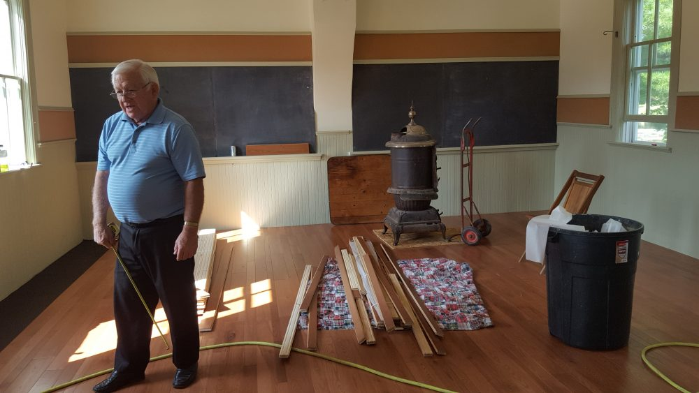 A board member restoring the school house after the fire